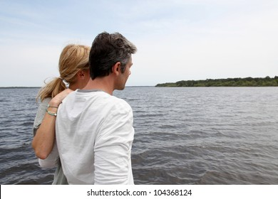 Profile view of couple sitting on a wooden bridge by a lake