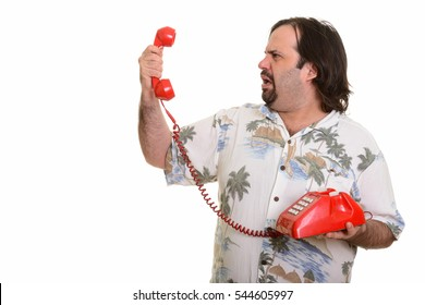 Profile view of fat Caucasian man holding old telephone looking angry isolated against white background