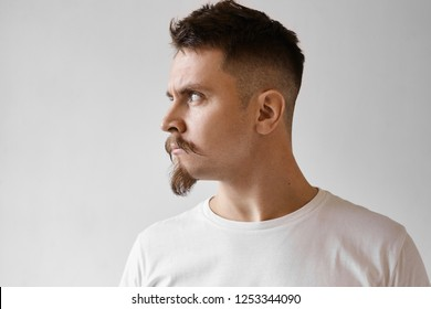 Profile view of fierce displeased young Caucasian male with goatee, mustache and stylish haircut poising isolated in white t-shirt looking away with angry offended expression, does not want to talk