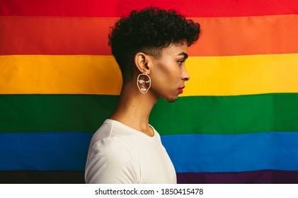 Profile view of gay man standing against pride flag. Transgender man wearing earring and makeup.