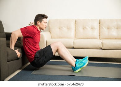 Profile view of a good looking athletic young man doing tricep dips leaning on a couch at home