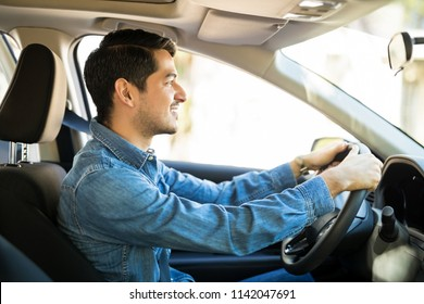 Profile view of an good looking young man driving a car and paying attention to the road, man wearing seat belts with both hands on steering wheel. Ideal driving condition.