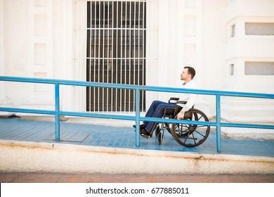 Profile view of a good looking young man going up a building ramp on a wheelchair