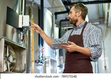 Profile view of handsome bearded technician wearing apron using digital tablet while adjusting equipment at modern brewery