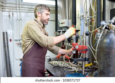 Profile view of handsome bearded worker wearing apron and gloves using bottle capper while working at modern brewery