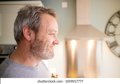 A profile view of a handsome man smiling in the kitchen