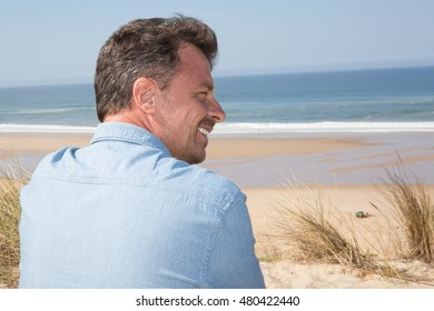 Profile view of a Handsome middle age man in casual clothing enjoying beach