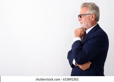 Profile view of handsome senior bearded businessman thinking while wearing eyeglasses against white background