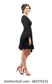 Profile view of happy smiling Hispanic woman in black flounce dress looking at camera. Full body length portrait isolated on white background.