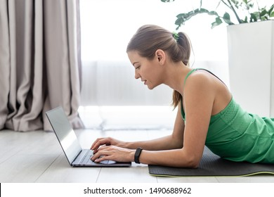 Profile view of happy sporty and young adult woman in sportswear lying on floor at fitness mat and using laptop computer