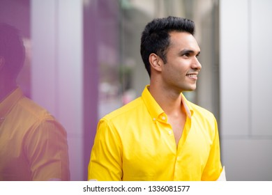 Profile view of happy young handsome Indian man smiling in the city