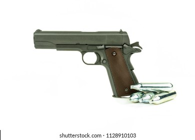 Profile view of isolated semi-automatic airsoft handgun with gas container. Replica of real handgun on white background.