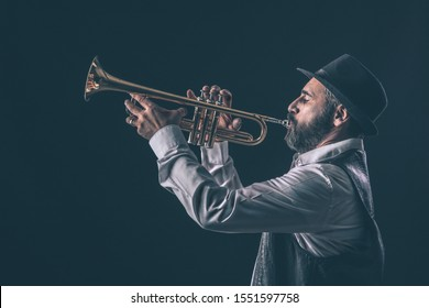 profile view of a jazz trumpet player with beard and hat.black background.