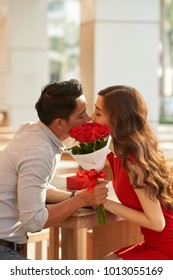 Profile view of kissing Asian couple sitting at outdoor cafe and celebrating anniversary, handsome young man holding bouquet of red roses in hand