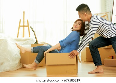 Profile view of lovely Asian couple having fun while riding in cardboard box at new apartment, interior design items and moving boxes on background