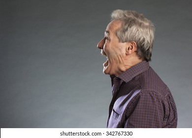 Profile view of male senior shouting. Horizontal portrait on gray background with copy space