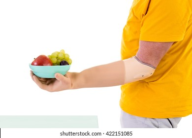 Profile View of Man with Prosthetic Arm Wearing Bright Yellow T-Shirt Holding Small Bowl of Fresh Fruit in Studio with White Background and Copy Space