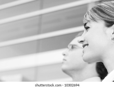 profile view of man and woman standing looking in same direction in front of office building.
