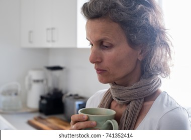 Profile view of middle aged woman with grey hair and scarf holding green cup in kitchen looking worried (selective focus)