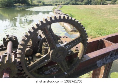 profile view on a large wheel of a rusty lock above the Doubs river in Franche Comté, France