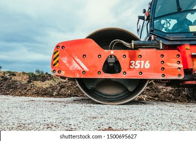Profile view of orange steamroller. Close-up view of road roller on gravel road.