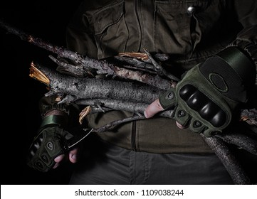 Profile view photo of a male person in brown tactical outfit jacket and gloves holding wood branches and knife on black background.