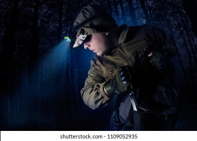 Profile view photo of a male person in brown tactical outfit jacket, gloves, backpack and head flashlight taking out knife on night woods background.