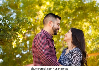 Profile view of a pretty Latin couple looking at each other and about to kiss at a park