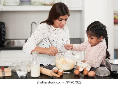 Profile view of pretty little girl with two braids adding flour into bowl while cooking appetizing pie with mom, interior of modern kitchen on background