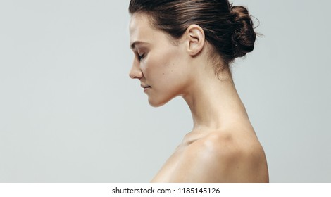Profile view of pretty young woman topless. Beautiful caucasian woman against grey background with eyes closed.