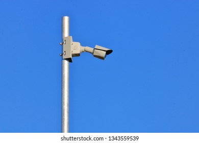 Profile view of small electronic surveillance security camera mounted on exterior metal pole against chromatic blue.