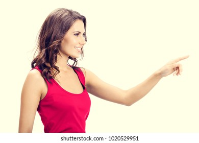 Profile view of smiling beautiful young woman in casual smart red clothing, showing copyspace, visual imaginary or something, or pressing virtual button.