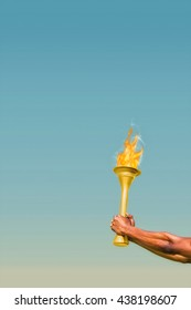 Profile view of sportsman holding a cup against blue sky