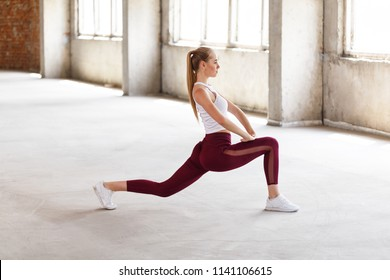 Profile view of sporty long-hair girl doing lunges working-out leg muscles and glutes in loft interior