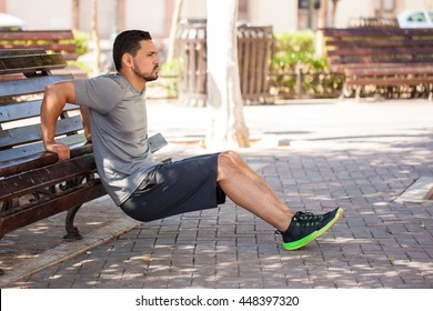 Profile view of a strong man exercising his arms and doing tricep dips outdoors in a park bench