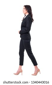 Profile view of successful female ceo in black suit walking and looking forward. Full body isolated on white background.