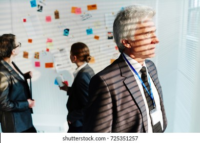 Profile view of thoughtful senior FBI agent looking out of window while his female colleagues investigating circumstances of crime