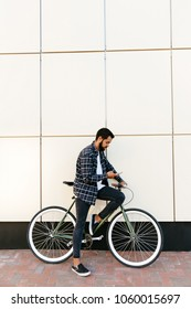 Profile view of a trendy bearded hipster man using a mobile phone while sitting on bicycle, on the city street, near the urban wall. Dressed in shirt, jeans and moccasins.