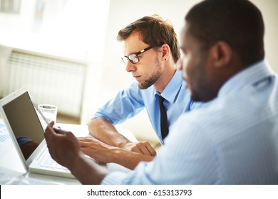 Profile view of two confident financial managers sitting in spacious office and making corrections in annual accounting reports
