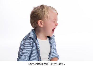 A profile view of a two year old boy crying. Shot in the studio on a white, backdrop.