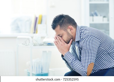 Profile view of upset young patient covering his face with hands after his highly professional physician revealed him hopeless diagnosis