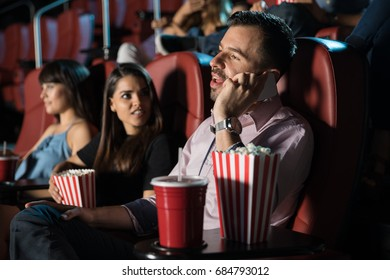 Profile view of a very obnoxious and disrespectful man talking on the phone while sitting in a movie theater