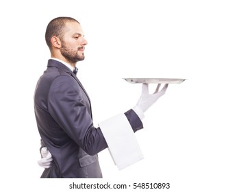 Profile view of a waiter in tuxedo and gloves holding empty tray and napkin over white background