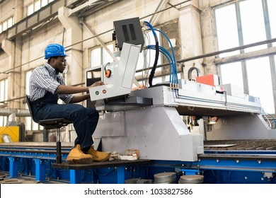 Profile view of young African American worker wearing overall and checked shirt operating machine unit at production department of modern plant