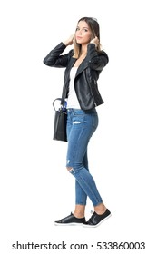 Profile view of young attractive woman in wearing jeans, leather jacket and bag adjusting hair with hands.  Full body length standing portrait isolated over white background.