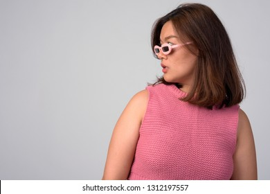 Profile view of young beautiful Asian woman with novelty glasses