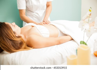 Profile view of a young brunette getting a deep tissue massage at a health and beauty spa