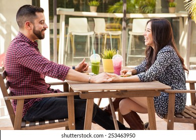 Profile view of a young couple holding hands during a lunch date and having fun