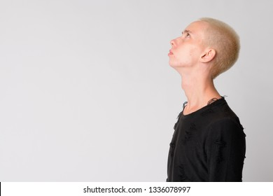 Profile view of young handsome androgynous man looking up