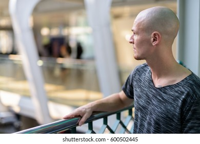 Profile view of young handsome bald man thinking on the foot bridge in city center of Bangkok Thailand